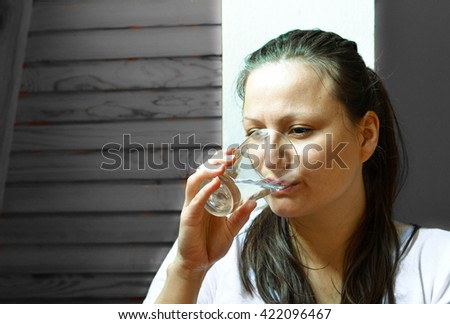 Woman drinking the glass of water at home - stock photo
