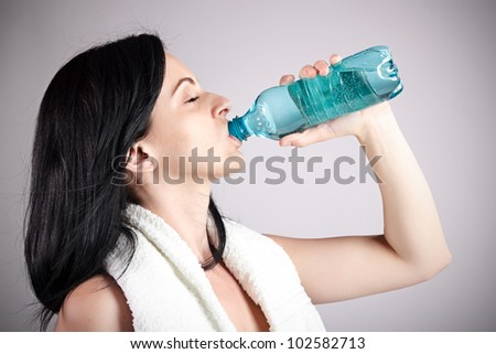 Woman drinking water after training - stock photo