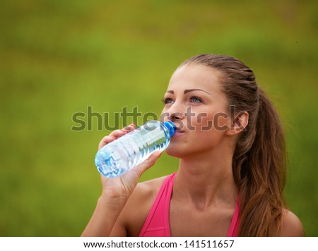 Woman drinking water from a bottle in nature - stock photo