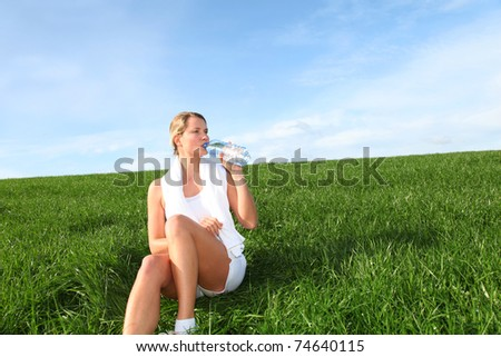 Woman drinking water from water during fitness activity - stock photo