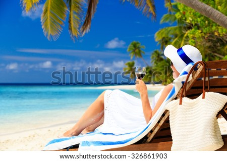 woman drinking wine on tropical beach resort - stock photo