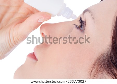 woman dripping eye with eyes drops - stock photo