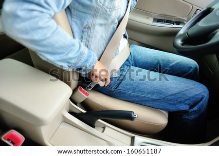 woman driver buckle up the seat belt before driving - stock photo