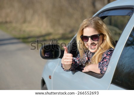 Woman driver happy smiling showing thumbs up coming out of car window  - stock photo