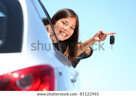 Woman driver holding car keys driving her new car. Beautiful multiracial young woman. - stock photo