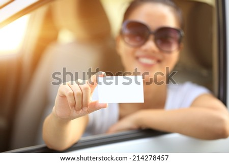 woman driver sit in car hold one blank business card  - stock photo