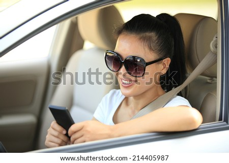 woman driver use her cell phone in car - stock photo