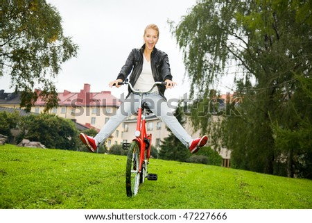 Woman driving a bike in the park - stock photo