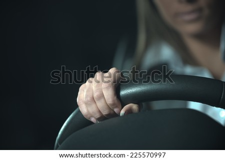 Woman driving a car late at night, hands on steering wheel close-up. - stock photo