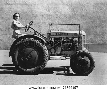 Woman driving a tractor - stock photo