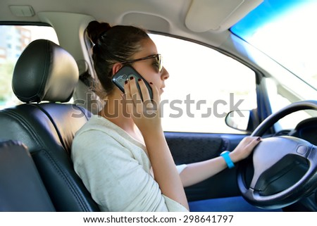 Woman driving and talking by cellular phone  - stock photo