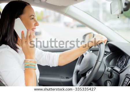 Woman driving and talking on the phone  - stock photo