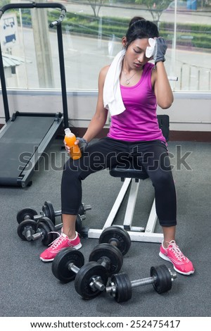 Woman drying her sweat with towel in the gym - stock photo