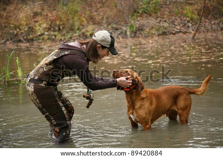 Woman Duck Hunter petting Labrador Retriever in Pond - stock photo