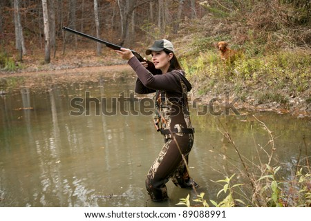 Woman Duck Hunter wearing Camo Waders with Rifle in Pond and Dog in Background - stock photo
