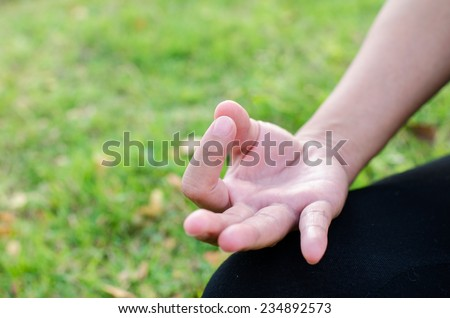 woman during relaxation and meditation in park meditation session. Frame shows half of arm with copyspace. - stock photo
