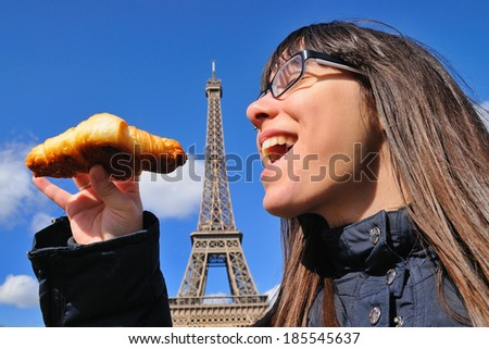 Woman eating a croissant in front of the Eiffel Tower. - stock photo
