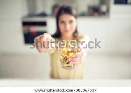 Woman eating and offering homemade organic mix fruit salad.Fruit diet,dieting,nutrition,vegetarian concept.Food for better skin,strong immune system,diet fitness meal.Healthy snack.Focus on the cup - stock photo
