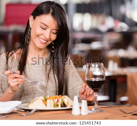 Woman eating at a restaurant looking very happy - stock photo