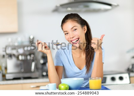 Woman eating breakfast cereals drinking orange juice smiling happy in the morning. Beautiful young multiracial woman sitting in her kitchen at home. Mixed race Asian Caucasian female model. - stock photo