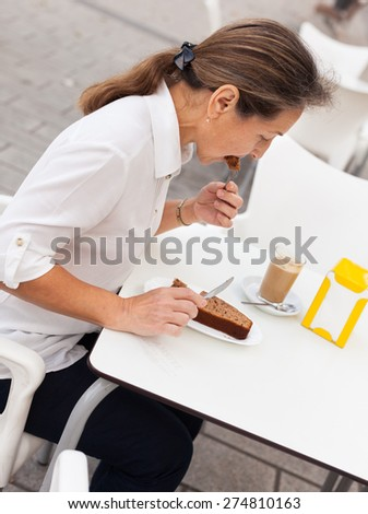 Woman  eating cake  at  cafe table with white.  - stock photo