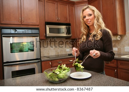 Woman eating dinner in her luxury kitchen - stock photo