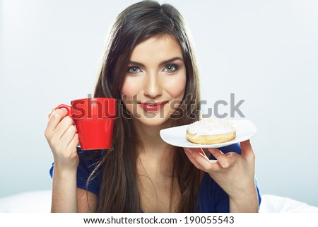 Woman eating donut in bed with coffee cup. Smiling girl. - stock photo