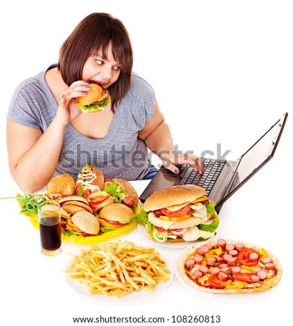 Woman eating fast food at working pc. Isolated. - stock photo