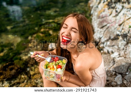 Woman eating healthy salad from plastic container near the river - stock photo