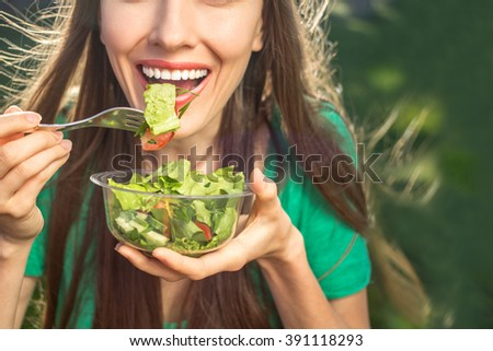 Woman eating healthy salad from plastic container over green grass with flying hair on a sunny spring day. backlight - stock photo