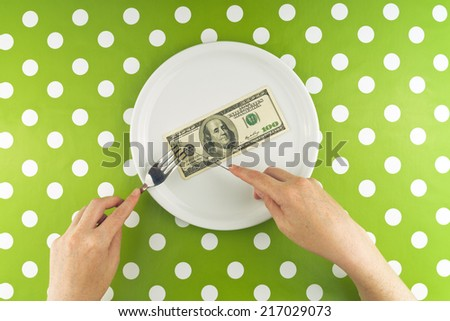 Woman eating hundred dollar bill for dinner, top view above polka dotted table cloth - stock photo