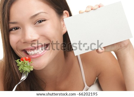 Woman eating salad showing blank sign with copy space. Healthy eating concept with young asian woman smiling looking at camera. Copyspace for text. - stock photo