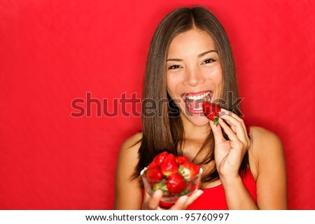 Woman eating strawberries happy. Pretty girl eating healthy snack on red background. Attractive Asian Caucasian female model joyful. - stock photo