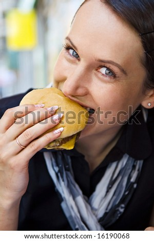 woman eating tasty hamburger at outdoor - stock photo