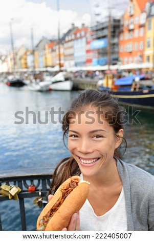 Woman eating traditional danish fast food snack hot dog. Girl enjoying hot dogs outside in Nyhavn waterfront canal street of Copenhagen, Denmark. - stock photo