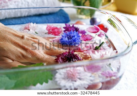 Woman elderly hand lies in a glass basin with warm mint, rose petals and colorful cornflowers water during a hands care course in a spa-centre - stock photo