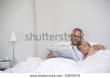 Woman embracing man reading paper in bed - stock photo