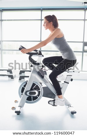 Woman energetically riding exercise bike in gym - stock photo
