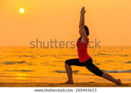 woman engaged in yoga at sunset near the ocean - stock photo