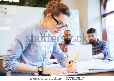 Woman engineer working on blueprint in office with colleagues on background - stock photo