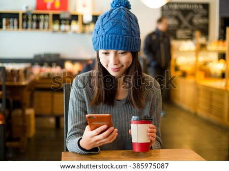 Woman enjoy her coffee and look at mobile phone - stock photo