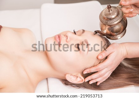 Woman enjoying a Ayurveda oil head massage treatment in spa - stock photo