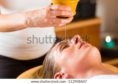 Woman enjoying a Ayurveda oil massage treatment in a spa - stock photo