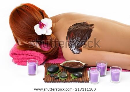 Woman enjoying a chocolate beauty treatment at the health spa - stock photo