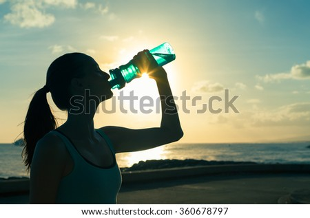Woman enjoying a refreshing drink of water.  - stock photo