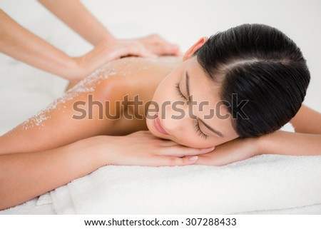 Woman enjoying a salt scrub massage at the health spa - stock photo