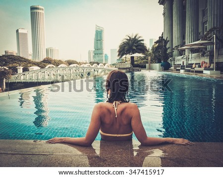 Woman enjoying a swim in a luxurious high rise pool. - stock photo