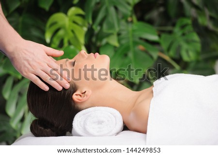 Woman enjoying a wellness head massage in a spa - stock photo