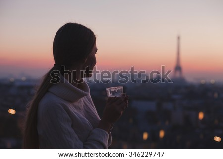 woman enjoying beautiful panoramic view of Paris with cup of coffee, cozy evening in cafe - stock photo