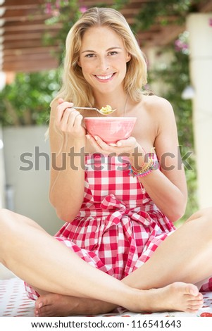 Woman Enjoying Bowl Of Breakfast Cereal - stock photo
